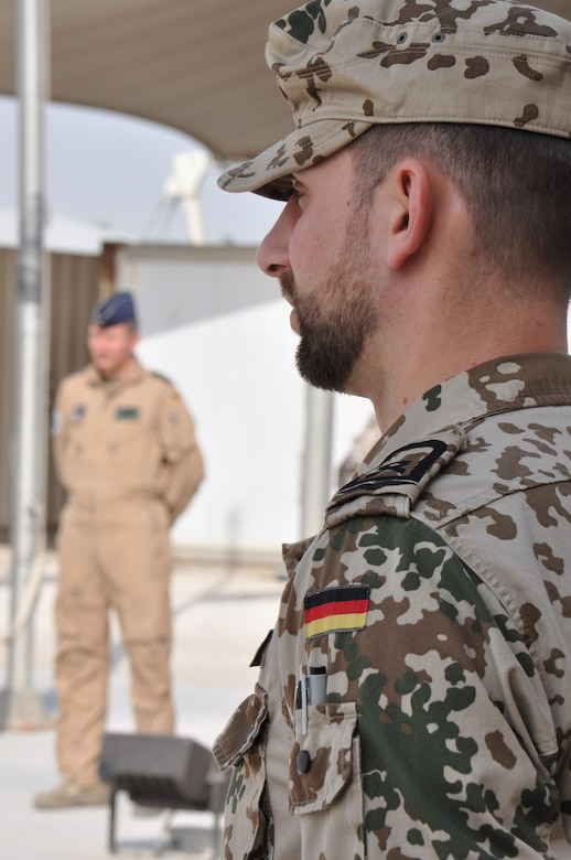 A member of the German Air Force stands at attention as he waits for the raising of the German flag during a ceremony at Al Udeid Air Base, Qatar, Feb. 8, 2016. The ceremony recognized the addition of Germany to the Operation Inherent Resolve coalition. (U.S. Air Force photo by Tech. Sgt. James Hodgman/Released)