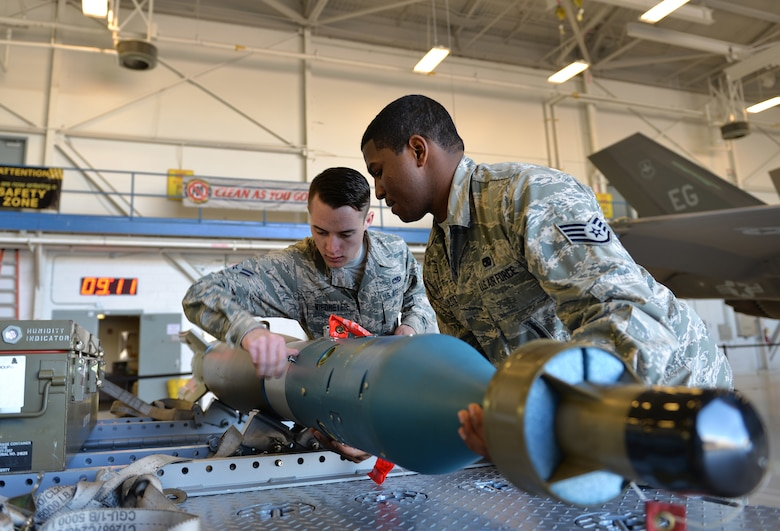 Staff Sgt. Timothy Gaulden, a 33rd Aircraft Maintenance Squadron weapons load crew chief, and Airman 1st Class Jacob Robinson, a 33rd AMXS weapons load crew member, attach a joint direct attack munition to a missile-guided bomb unit for the first F-35A Lightning II load competition at Eglin Air Force Base, Fla., Feb. 5, 2016. During the event, Airmen competed in a uniform inspection, a written test, a tool box inspection, and an integrated load. (U.S. Air Force photo/Senior Airman Andrea Posey)