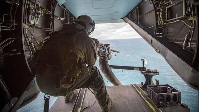 Lance Cpl. Jarod L. Smith, a crew chief with Marine Medium Tiltrotor Squadron 365, fires a mounted M2 Browning .50-caliber machine gun from the back of the MV-22B Osprey during a live fire training session off the coast of Marine Corps Air Station New River, N.C., Feb. 10, 2016. Marines with VMM-365 flew to a landing zone, which allowed pilots to practice CALs in their Osprey's and then flew several miles off the coast to practice their proficiency with the .50-caliber  machine gun.