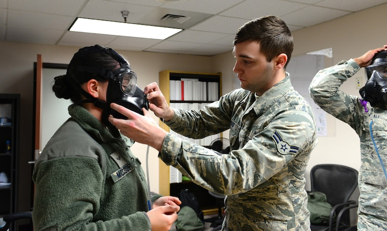 U.S. Air Force Airman 1st Class Chasten Gibbs, 354th Medical Group bioenvironmental engineering apprentice, helps Airmen put their masks on for fit testing, Feb. 3, 2016 at Eielson Air Force Base, Alaska. Fit testing is done to ensure Airmen have properly fitting masks so there is no exposure to chemical warfare agents or respirable particulates.  (U.S. Air Force photo by Airman 1st Class Cassandra Whitman/Released)