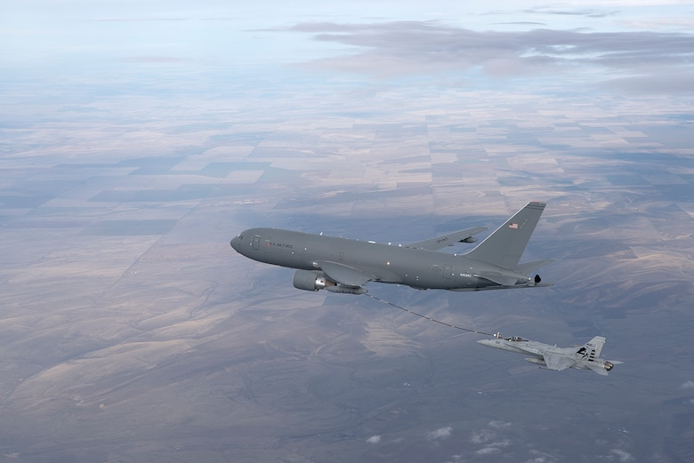 A KC-46A Pegasus refuels an F/A-18 Hornet with its hose and drogue system. (Boeing photo/John Parker)