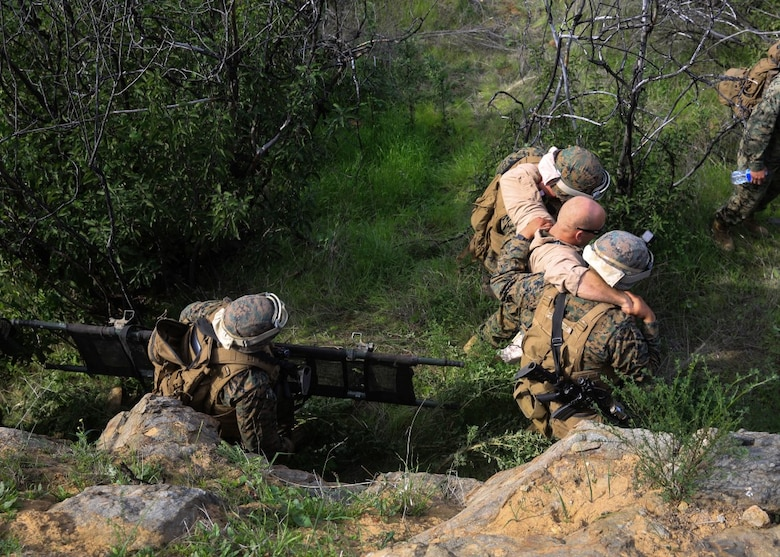 A Marine aid and litter team retrieves a simulated down pilot during a tactical recovery of aircraft and personnel, or TRAP, training scenario at Camp Pendleton, Calif., Feb. 10, 2016. In preparation for their upcoming deployment with the 31st Marine Expeditionary Unit, the TRAP scenario offers the Marines of Weapons Company, 2nd Battaion, 4th Marine Regiment, 1st Marine Divison, a secondary skillset in additon to their own primary duties, refining their ability to efficiently conduct a recovery mission. (U.S. Marine Corps photo by Lance Cpl. Devan K. Gowans/Released)