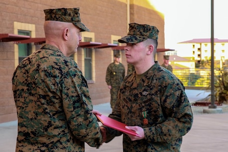 Cpl. Corey Mount is recognized by Lt. Gen. David Berger as the I Marine Expeditionary Force Marine of the Year during a ceremony at Camp Pendleton Feb. 10, 2016. The award recognizes a Marine who exceeds expectations and embodies the spirit and ideals of the Marine Corps. Berger is the I MEF commanding general and Mount, a native of Indianapolis, is an administrative noncommissioned officer with 1st Reconnaissance Battalion, 1st Marine Division, I MEF. (U.S. Marine Corps photo by Lance Cpl. Caitlin Bevel)