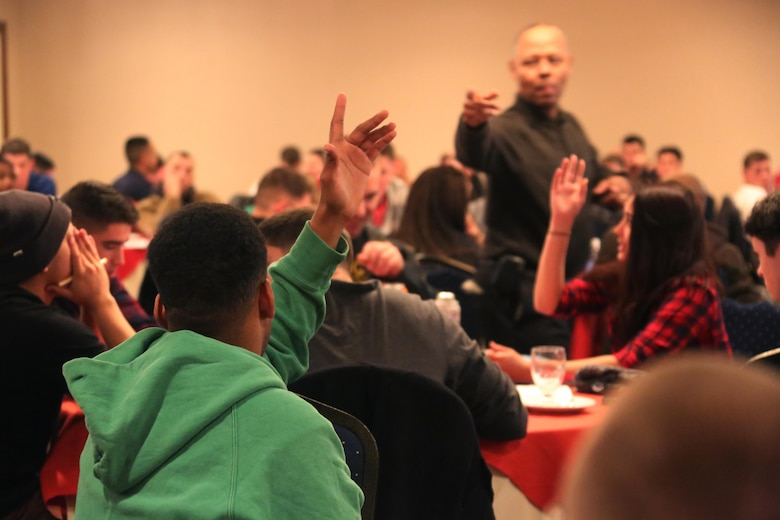 A crowd of service members raise their hands during an interactive exercise during a Single Marine and Sailor Personal Growth Retreat in New Bern, N.C., Jan. 29-30, 2016. Marines and Sailors from across 2nd Marine Aircraft Wing gathered for a detailed seminar that encompassed basic skills like coping with stress, relationship building and self-awareness. The seminar was led by chaplains with 2nd MAW and focused on helping Marines and Sailors grow as individuals to get them mentally ready for forward deployment and to promote self-improvement.  (U.S. Marine Corps photo by Cpl. N.W. Huertas/Released)