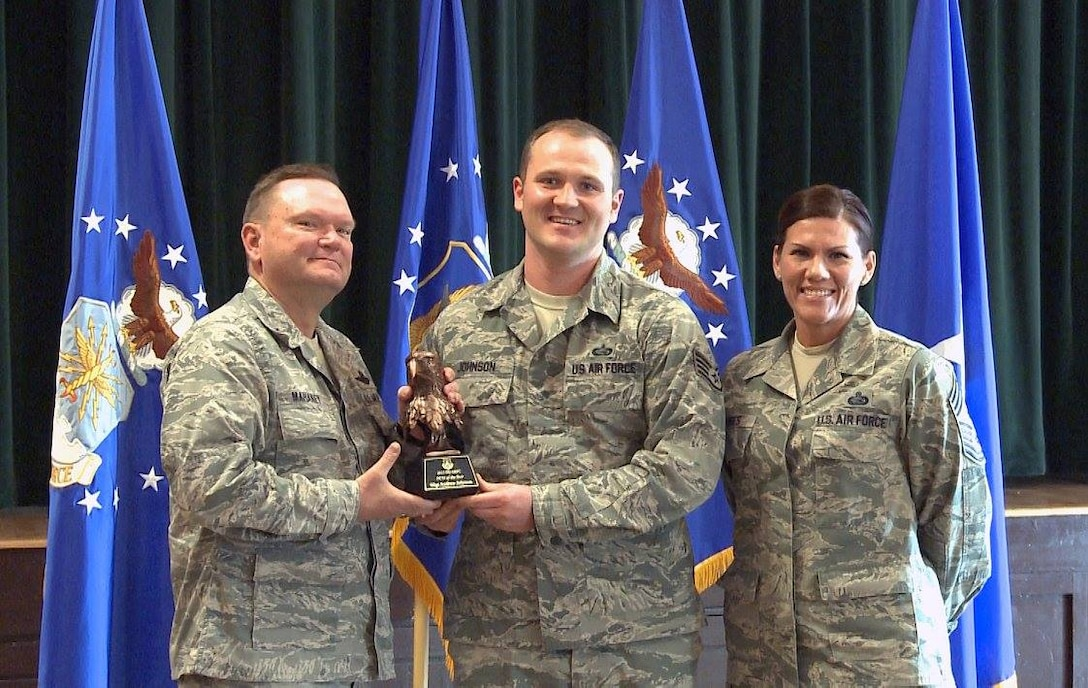 "Brig. Gen. Samuel ""Bo"" Mahaney, Air Reserve Personnel Center commander, and Chief Master Sgt. Ruthe Flores, ARPC command chief, present the ARPC Noncommissioned Officer of the Year award to Staff Sgt. Andrew Johnson. Mahaney honored ARPC's 2015 outstanding performers of the year Feb. 16, 2016, at the Heritage Eagle Bend Country Club in Aurora, Colo. (U.S. Air Force photo/Quinn Jacobson)"