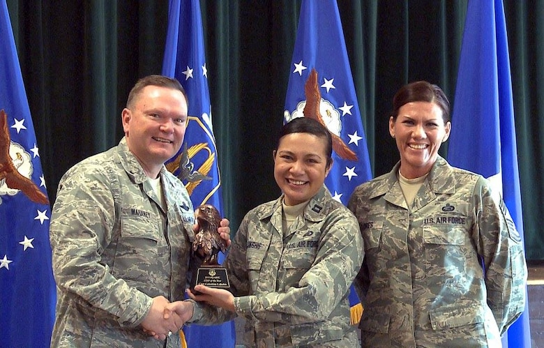 "Brig. Gen. Samuel ""Bo"" Mahaney, Air Reserve Personnel Center commander, and Chief Master Sgt. Ruthe Flores, ARPC command chief, present the ARPC Company Grade Officer of the Year award to Capt. Celestine Lukshis. Mahaney honored ARPC's 2015 outstanding performers of the year Feb. 16, 2016, at the Heritage Eagle Bend Country Club in Aurora, Colo. (U.S. Air Force photo/Quinn Jacobson)"