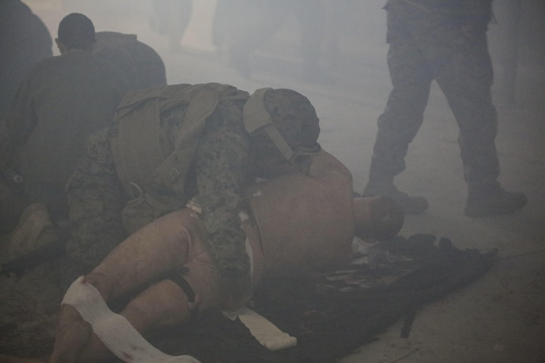 U.S. Navy Seaman Justin Phares, a hospitalman with 2nd Medical Battalion, treats a casualty during a tactical combat casualty care exercise at Camp Lejeune, N.C., Feb. 12, 2016. Sailors were challenged by a chaotic environment of smoke and loud, sporadic noises. (U.S. Marine Corps photo by Cpl. Paul S. Martinez/Released)