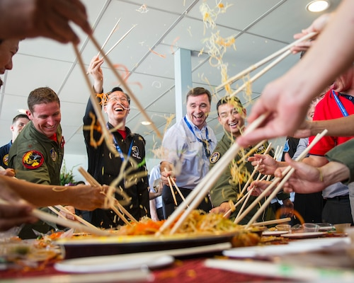 "Aerial demonstration team members from the U.S., Singapore, Republic of Korea, Malaysia and France partake in the Lunar New Year tradition of a ""Lo Hei"" salad toss during a patch exchange ceremony prior to the Singapore International Airshow, at Changi Airport, Singapore, Feb. 14, 2016. The custom is meant to bring good fortune for the new year and offered Airmen from several nations a fun experience to launch them into the airshow. The Singapore International Airshow is focused on building stronger relationships between the U.S., Singapore and the international community. (U.S. Air Force photo by Capt. Raymond Geoffroy/Released)"