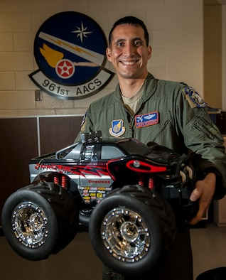 U.S. Air Force Capt. Costas Dracopoulos, 961st Airborne Air Control Squadron flight safety officer, holds a toy car in front of his squadron emblem Feb. 17, 2016, at Kadena Air Base, Japan. Having been personally affected, Dracopoulos organized a toy drive to send toys to the families of the victims of the San Bernardino shootings. The 961st AACS sent more than 50 toys in less than a week to support the families. (U.S. Air Force photo by Airman 1st Class Corey M. Pettis)