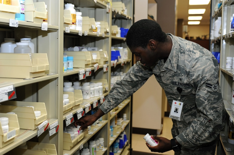 Airman 1st Class Darius Longmire, 28th Medical Support Squadron pharmacy technician, removes a bottle of Vitamin D from the pharmacy stock shelf at Ellsworth Air Force Base, S.D., Jan. 13, 2016. Pharmacy technicians remove medication to fill prescriptions for customers, and fill an average of 13,000 per month, including new scripts and refills. (U.S. Air Force photo by Senior Airman Hailey R. Staker/Released)