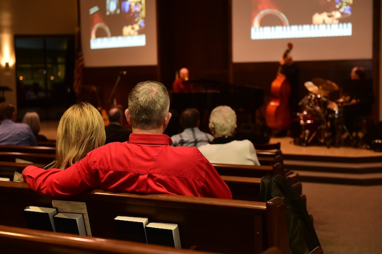 """A couple enjoys Danny Byram and his band Feb. 12, 2016, at the Buckley Chapel on Buckley Air Force Base, Colo. Nicknamed """"The Combat Musician,"""" Byram has performed at more than 100 U.S. military installations worldwide, more than any other Christian musician. (U.S. Air Force photo by Airman 1st Class Luke W. Nowakowski/Released)"""