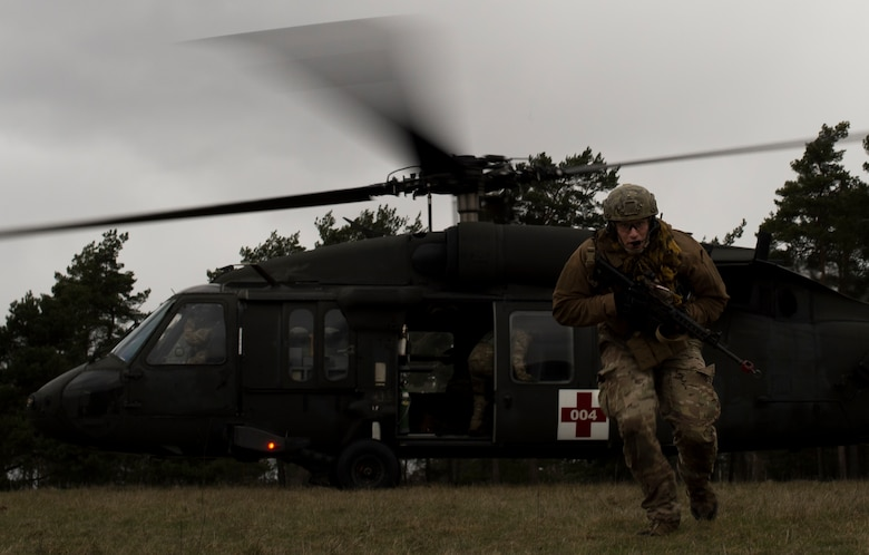 Senior Airman Tormod Lillekroken, 2nd Air Support Operations Squadron tactical air control party member, rejoins his team after helping a simulated casualty onto a UH-60 for medical evacuation during training at U.S. Army Garrison Bavaria in Vilseck, Germany, Feb. 8, 2016. The training consisted of calling in close air support, neutralizing opposing forces and practicing medical evacuation by helicopter. (U.S. Air Force photo/Senior Airman Jonathan Stefanko)