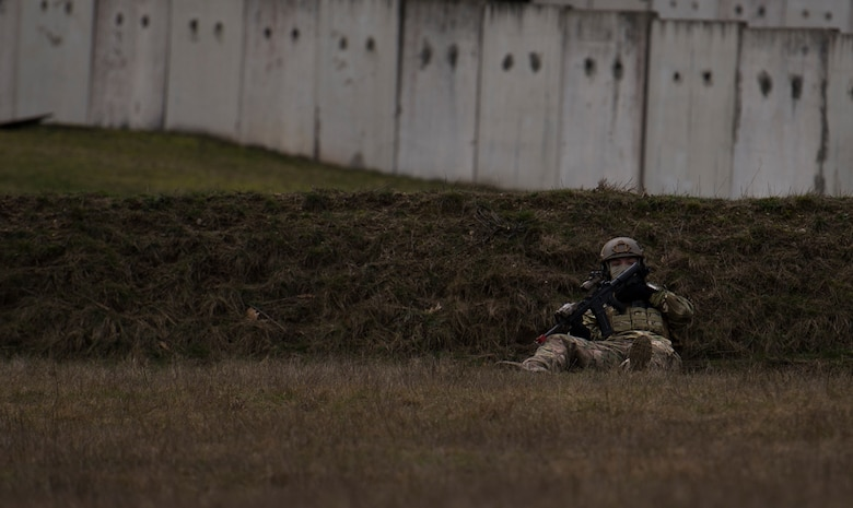 Senior Airman Martin Dietrich, 2nd Air Support Operations Squadron tactical air control party member, takes cover behind a hill during training at U.S. Army Garrison Bavaria in Vilseck, Germany, Feb. 8, 2016. The training consisted of Airmen calling in close air support, neutralizing opposing forces and practicing medical evacuation by helicopter. By conducting the training in an urban environment the ASOS team was forced to think about proper tactics to ensure they weren't caught in the line of fire. (U.S. Air Force photo/Senior Airman Jonathan Stefanko)