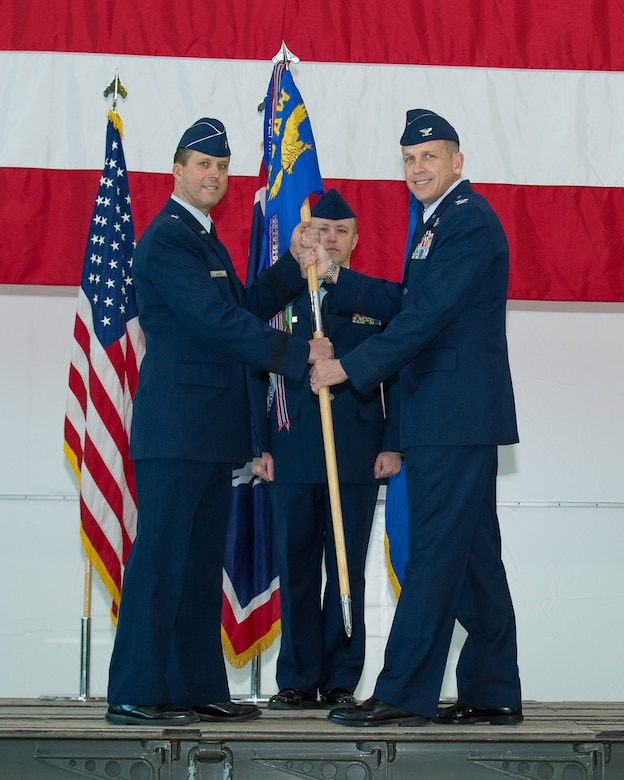 Wyoming Air National Guard Commander Brig. Gen. Stephen Rader passes the 153rd Airlift Wing guidon to incoming Wing Commander Col. Paul Lyman during a change of command ceremony, Feb. 13, 2016 in Cheyenne, Wyoming. (U.S. Air National Guard photo by Master Sgt. Charles Delano/released)