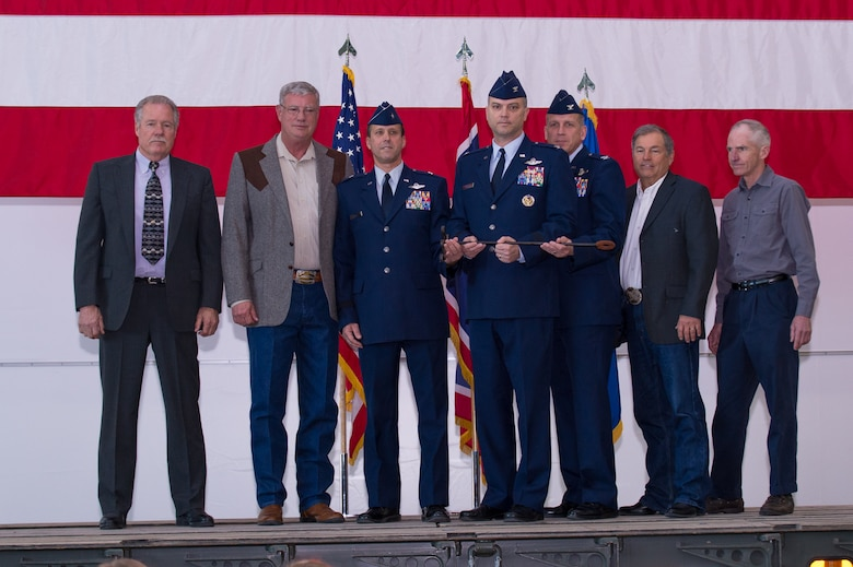 U.S. Air Force Col. Bradley Swanson, outgoing wing commander of the 153rd Airlift Wing, receives the Wyoming National Guard brand from former wing commanders, Wyoming Air National Guard Commander Brig. Gen. Stephen Rader and incoming Wing Commander Col. Paul Lyman during a change of command ceremony, Feb. 13, 2016 in Cheyenne, Wyoming. (U.S. Air National Guard photo by Master Sgt. Charles Delano/released)
