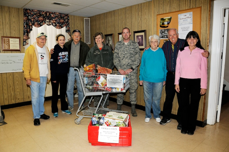 """U.S. Air Force Tech. Sgt. Dennis Puckett and 145th Wing Chaplain (Lt. Col.) Debra Kidd from the North Carolina Air National Guard, stand with volunteers after dropping off food items at the Loaves and Fishes food pantry in Charlotte, N.C., Feb. 12, 2016. During February's Unit Training Assembly, Airmen celebrated the Carolina Panthers and Super Bowl Sunday by participating in """"Souper"""" Bowl. """"Souper Bowl of Caring"""" utilizes Super Bowl weekend to rally people together in an effort to help fight hunger and poverty in their local communities. (U.S. Air National Guard photo by Master Sgt. Patricia F. Moran/Released)"""