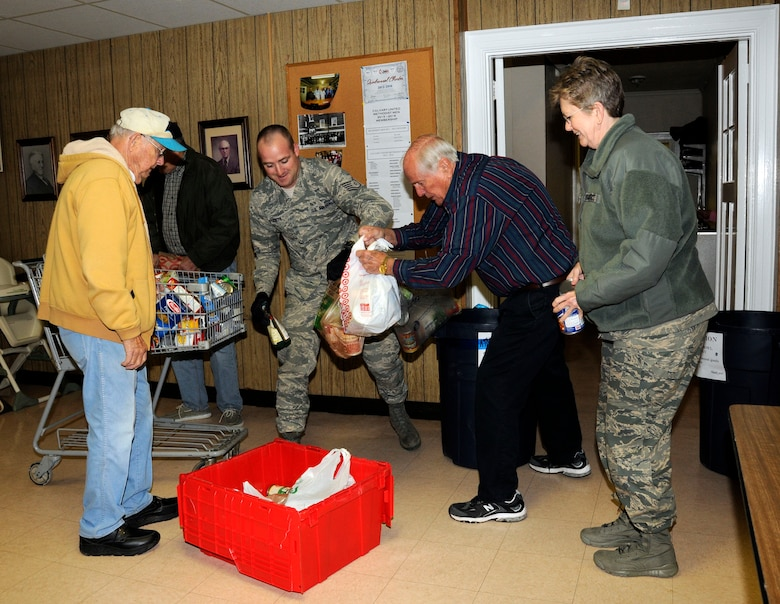 """U.S. Air Force Tech. Sgt. Dennis Puckett and 145th Wing Chaplain (Lt. Col.) Debra Kidd from the North Carolina Air National Guard, get help from volunteers as they dropped off food items at Loaves and Fishes food pantry in Charlotte, N.C., Feb. 12, 2016. During February's Unit Training Assembly, Airmen celebrated the Carolina Panthers and Super Bowl Sunday by participating in """"Souper"""" Bowl. """"Souper Bowl of Caring"""" utilizes Super Bowl weekend to rally people together in an effort to help fight hunger and poverty in their local communities. (U.S. Air National Guard photo by Master Sgt. Patricia F. Moran/Released)"""