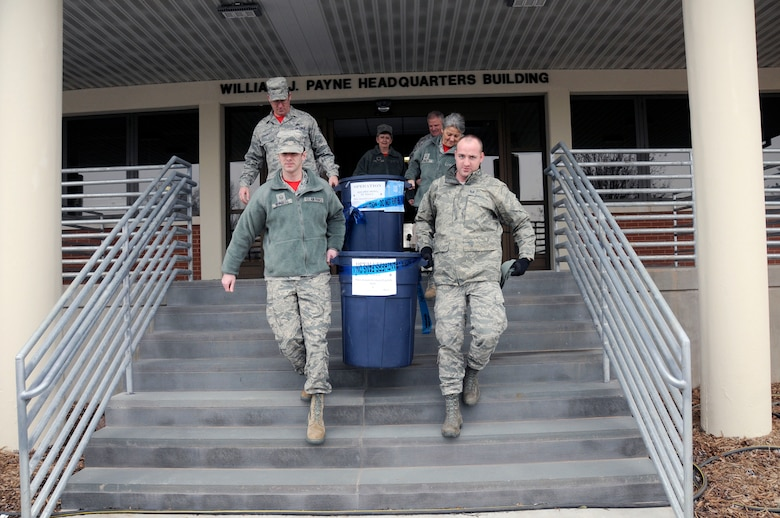 """U.S. Air Force Master Sgt. Noah Burgess, Tech. Sgt. Dennis Puckett, Senior Master Sgts. Johnathan Stallings and Sharon Fowler, all members of the 145th Mission Support Group, and Chaplain (Lt. Col.) Debra Kidd, chaplain, 145th Airlift Wing (AW), and Col. Marshall Collins, commander, 145th AW, carry containers filled with non-perishable food to a waiting van at the North Carolina Air National Guard Base, Charlotte Douglas International Airport, Feb. 12, 2016. During February's Unit Training Assembly, Airmen celebrated the Carolina Panthers and Super Bowl Sunday by participating in """"Souper"""" Bowl. """"Souper Bowl of Caring"""" utilizes Super Bowl weekend to rally people together in an effort to help fight hunger and poverty in their local communities. Donations went to Loaves and Fishes food pantry in Charlotte, N.C. (U.S. Air National Guard photo by Master Sgt. Patricia F. Moran/Released)"""