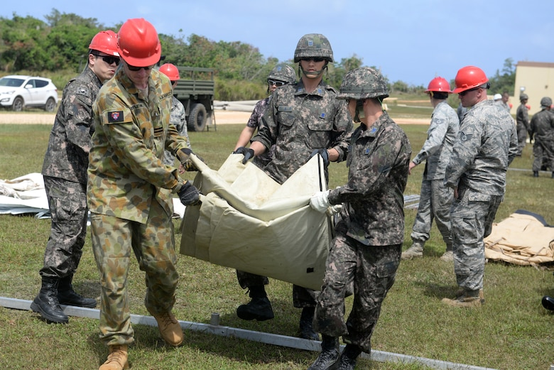 Airmen from the Royal Australian Air Force and the Republic of Korea Air Force carry a tarp during a tent building exercise Feb. 13, 2016, at Andersen Air Force Base, Guam. The exercise is a small part of the first multilateral Partner Nation Silver Flag, a U.S. Pacific Command multilateral Theater Security Cooperation Program subject matter expert exchange event designed to build partnerships and promote interoperability through the equitable exchange of civil engineer related information. (U.S. Air Force photo/Senior Airman Joshua Smoot)