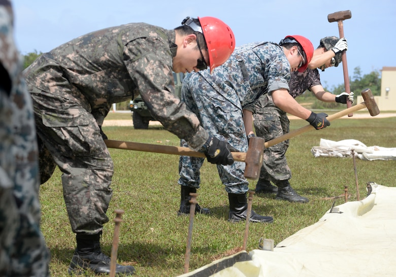 Airmen from the Republic of Korea Air Force and Japan Air Self-Defense Force hammer stakes to prepare a tent during Partner Nation Silver Flag Feb. 13, 2016, at Andersen Air Force Base, Guam. During the first multilateral Partner Nation Silver Flag, instructors from the 554th RED HORSE Squadron partnered with engineers from the Royal Australian Air Force, Republic of Singapore Air Force, ROKAF and the JASDF to exchange information on subjects from command and control, electrical, power production, heavy repair and emergency management. (U.S. Air Force photo/Senior Airman Joshua Smoot)