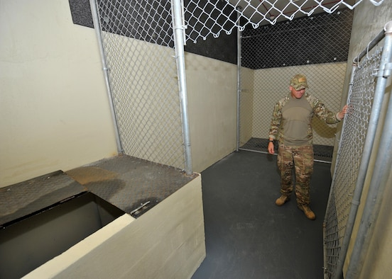 Royal Australian Air Force Leading Aircraftman Kevin Martins, Combat Support Unit 14 military working dog handler and trainer attached to the 380th Expeditionary Security Forces Squadron MWD Section, inspects a kennel in the newly constructed K9 compound at an undisclosed location in Southwest Asia, Jan. 26, 2016. The kennels are approximately 160 percent larger than those previous utilized and include a house for military working dogs to rest and relax. (U.S. Air Force photo by Staff Sgt. Kentavist P. Brackin/released)