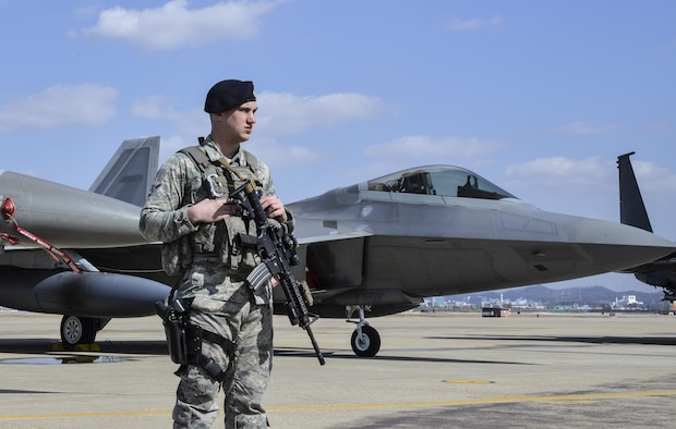 An Air Force Security Forces member stands guard next to an F22 Raptor fighter aircraft from Kadena Air Base, Japan, after it conducted a flyover in the vicinity of Osan Air Base, South Korea, in response to recent provocative action by North Korea Feb. 17, 2016. It was joined by three other Raptors, four F-15 Slam Eagles and four U.S. Air Force F-16 Fighting Falcons. The F-22 is designed to project air dominance rapidly and at great distances and currently cannot be matched by any known or projected fighter aircraft.  (U.S. Air Force photo by Tech. Sgt. Travis Edwards/Released)