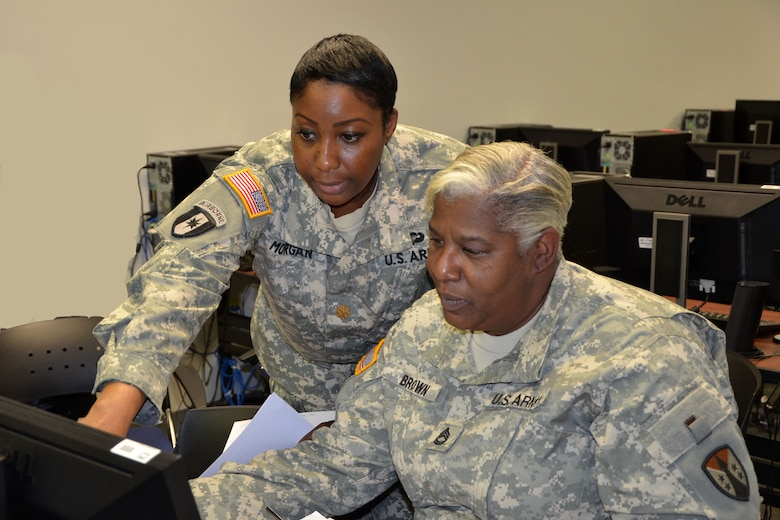 Maj. Camille Morgan, security manager and safety officer for the 915th Contracting Battalion out of Baltimore, shows Sgt. 1st Class Pamela Brown, contracting specialist, also with the 915th, how to process a de-obligation during battle assembly.