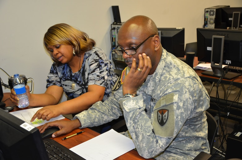 Shawn Willie, contracting specialist with the United States Army Corps of Engineers Huntsville Center, coaches team leader Lt. Col. Ronald Clark with the 917th Contracting Battalion out of San Antonio, on the final steps of a contract closeout. Select Soldiers of the Army Reserve Sustainment Command's 915th and 917th Contracting Battalions are partnering with USACE during their monthly battle assembly to teach and train Soldiers on contracting actions to help build their skillset.