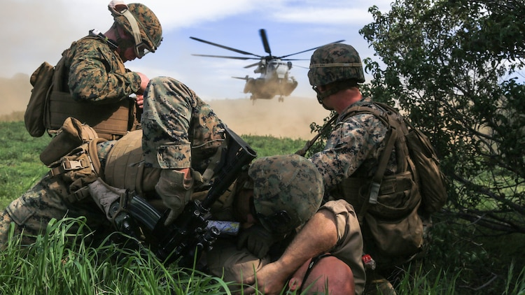 Marines protect a simulated injured person from the rotor wash of a CH-53E Super Stallion transport helicopter during a tactical recovery of aircraft and personnel, or TRAP, training scenario at Camp Pendleton, Feb. 10, 2016. TRAP is used to tactically recover personnel, equipment or aircraft by inserting the recovery force to the objective location. The Marines are with Weapons Company, 2nd Battalion, 4th Marine Regiment, 1st Marine Division. (U.S. Marine Corps photo by Lance Cpl. Devan K. Gowans/Released)