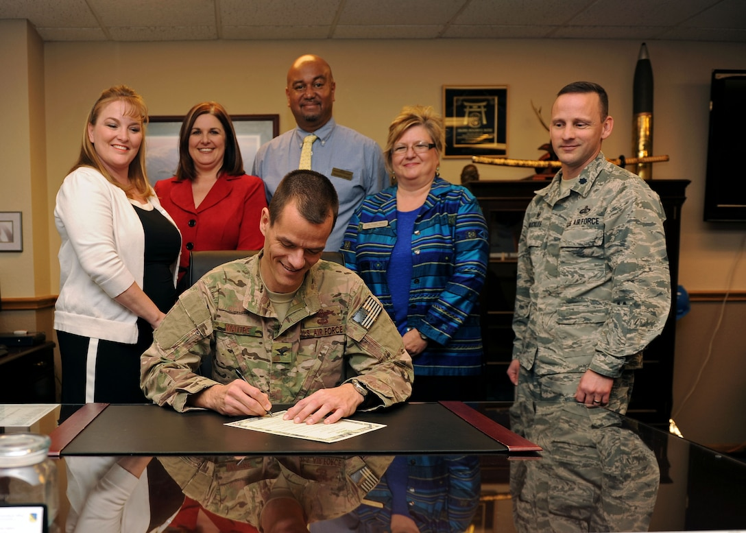 Col. Ben Maitre, 27th Special Operations Wing commander, signs a proclamation designating Feb. 22 through Feb. 27 as Military Saves Week, with members of the 27th Special Operations Force Support Squadron's Airman & Family Readiness Center financial planning team looking on, Feb. 11, 2016 at Cannon Air Force Base, N.M. Military Saves Week provides an opportunity for members of the military community to come together with federal, state and local resources to focus on the financial readiness of military members and their families, helping them to reduce debt and save their money. (U.S. Air Force photo/Staff Sgt. Whitney Amstutz)