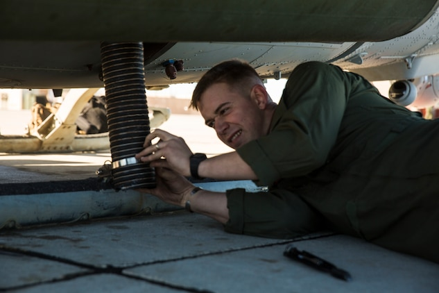 "Sgt. Benjamin Hebert, a crew chief with Marine Light Attack Helicopter Squadron 469 (HMLA-469) based out of Marine Corps Air Station Camp Pendleton, Calif., performs maintenance on a UH-1Y ""Venom"" helicopter aboard Marine Corps Air Station Yuma, Ariz., Friday, Feb. 5, 2016."
