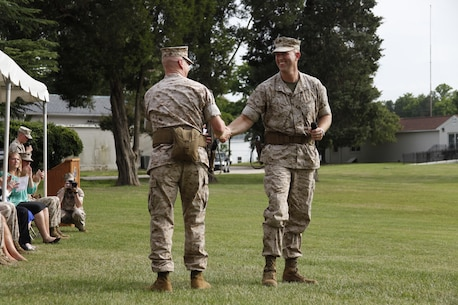 U.S. Marine Col. James M. Bright, outgoing regimental commanding officer, Marine Corps Security Force Regiment, left, shakes the hand of Col. Jown W. Evans, incoming regimental commanding officer, right, as he prepares to speak to invited guests during the Marine Corps Security Force Regiment change of command aboard Naval Weapons Station Yorktown, Va., June 19, 2015. The Marine Corps Security Force Regiment serves as support for anti-terrorist operations worldwide and the security of high value nuclear assets. (U.S. Marine Corps photo by Sgt. Esdras Ruano/Released)