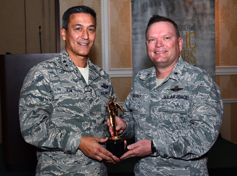 """Maj. Gen. Michael Kim, mobilization assistant to the Commander, Air Force Reserve Command, presents the Public Affairs Champion award to Brig. Gen. Samuel """"Bo"""" Mahaney, Air Reserve Personnel Center commander, at the Public Affairs Leadership Symposium held Feb. 9, 2016, in Marietta, Ga. This award recognizes commanders who are highly supportive and involved in the Public Affairs career field. (U.S. Air Force photo/Don Peek)"""