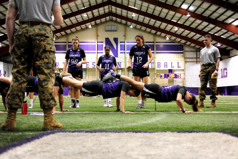 Capt. Daniel Cartica (standing right), Marine officer instructor at Northwestern University, observes Northwestern University female lacrosse players performing squad push-ups at the training event he helped organize at the university's indoor training facility, Feb. 16., 2016. Cartica holds the current world record for the World Marathon Challenge, which involves running seven marathons, on all seven continents in seven consecutive days.