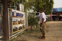A student at the Ban Phrom Nimit Middle School looks at a poster, during a dedication ceremony, in Wang Yeng Nam, Thailand, during exercise Cobra Gold, Feb. 16, 2016. Cobra Gold, in its 35th iteration, includes a specific focus on humanitarian civic action, community engagement, and medical activities conducted during the exercise to support the needs and humanitarian interests of civilian populations around the region.