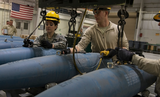 Staff Sgt. Nick Olmsted, 366th Equipment Maintenance Squadron crew chief, and Airman 1st Class Rachel Parker, 366th EMS crew member, unhook guided bomb unit-12 Paveway IIs from a crane, Feb. 8, 2016, at Mountain Home Air Force Base, Idaho. Members of the 366th EMS assembled GBU-12s to be used by the F-35A Lightning IIs during their first simulated deployment currently underway at Mountain Home AFB. (U.S. Air Force photo by Airman Chester Mientkiewicz/RELEASED)