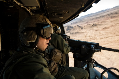"""Sgt. Benjamin Hebert, a crew chief with Marine Light Attack Helicopter Squadron 469 (HMLA-469), based out of Marine Corps Air Station Camp Pendleton, Calif., observes and verifies hits as Sgt. Daniel O'Niel, an aerial observer, fires a GAU-21 machine gun from a UH-1Y """"Venom,"""" during exercise """"Scorpion Fire,"""" at the Chocolate Mountain Aerial Gunnery Range, Friday, Feb. 5, 2016."""