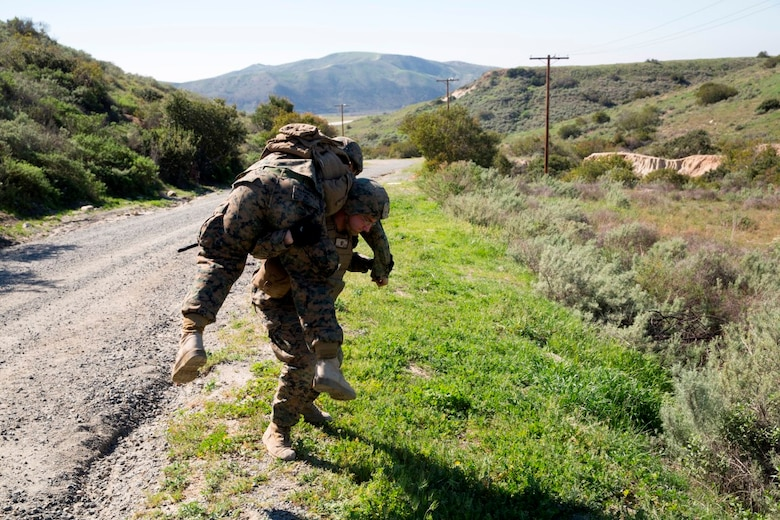Lance Cpl. Brandon Larue carries Cpl. Estelito Manansala a notional casualty during a counter-IED training exercise at Camp Pendleton, Feb. 12, 2016. This training is a part of a new Counter-IED Training Class developed by the Marine Corps Engineer School, Defeat the Device Branch, to improve operational readiness. Larue and Manansala are with Company A., 1st Combat Engineer Battalion, 1st Marine Division.