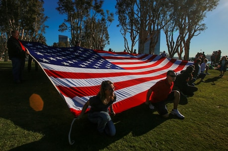 The family and friends of Marines and sailors deploying with the 13th Marine Expeditionary Unit display a large flag on the shore as the Boxer Amphibious Ready Group passes by in San Diego Feb. 12, 2016. The 13th MEU is capable of conducting amphibious operations, crisis response and limited contingency operations and is beginning an estimated six month deployment to the Western Pacific and Middle East. (U.S. Marine Corps photo by Lance Cpl. Caitlin Bevel)