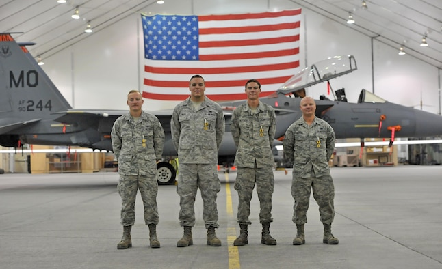 Senior Airmen Nash Camden, Matthew Mayo, Blake Destasio and Tech. Sgt. Kyle Martin, left to right respectively, pose for a photo after an awards ceremony at an undisclosed location in Southwest Asia, Feb. 16, 2016. The four Airmen were part of a group of nine maintainers from the 380th Expeditionary Aircraft Maintenance Squadron who were recognized for their efforts when they responded to a fire caused by a hydraulic fluid leak on an F-15E Strike Eagle fighter after it returned from a sortie December 2015. (U.S. Air Force photo by Staff Sgt. Kentavist P. Brackin/Released)