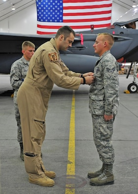 U.S. Air Force 1st Lt. Nicholas, F-15E Strike Eagle fighter pilot assigned to the 391st Expeditionary Fighter Squadron, pins an Air Force Commendation Medal on Senior Airman Nash Camden, a 380th Expeditionary Aircraft Maintenance Squadron weapons load crew member, during an awards ceremony at an undisclosed location in Southwest Asia, Feb. 16, 2016. Nicholas is one of two aircrew members who were inside a taxiing F-15 when a hydraulic fluid leak on the aircraft's hot brakes set it afire Dec. 2, 2015. (U.S. Air Force photo by Staff Sgt. Kentavist P. Brackin/Released)
