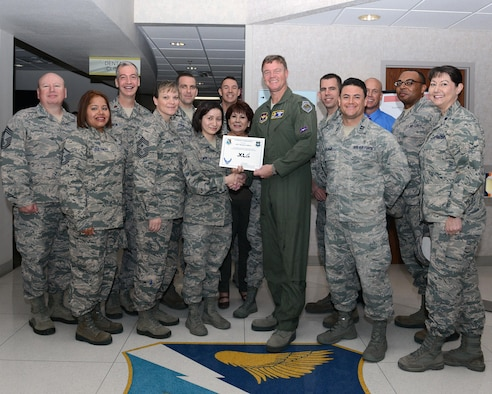 "Airman 1st Class Maritza Caldera, center, 47th Medical Operations Squadron mental health technician, accepts the ""XLer of the Week"" award from Col. Thomas Shank, right, 47th Flying Training Wing commander, and Chief Master Sgt. Teresa Clapper, left, 47th FTW command chief, here, Feb. 17, 2016. The XLer is a weekly award chosen by wing leadership and is presented to those who consistently make outstanding contributions to their unit and Laughlin. (U.S. Air Force photo by Senior Airman Jimmie D. Pike)"