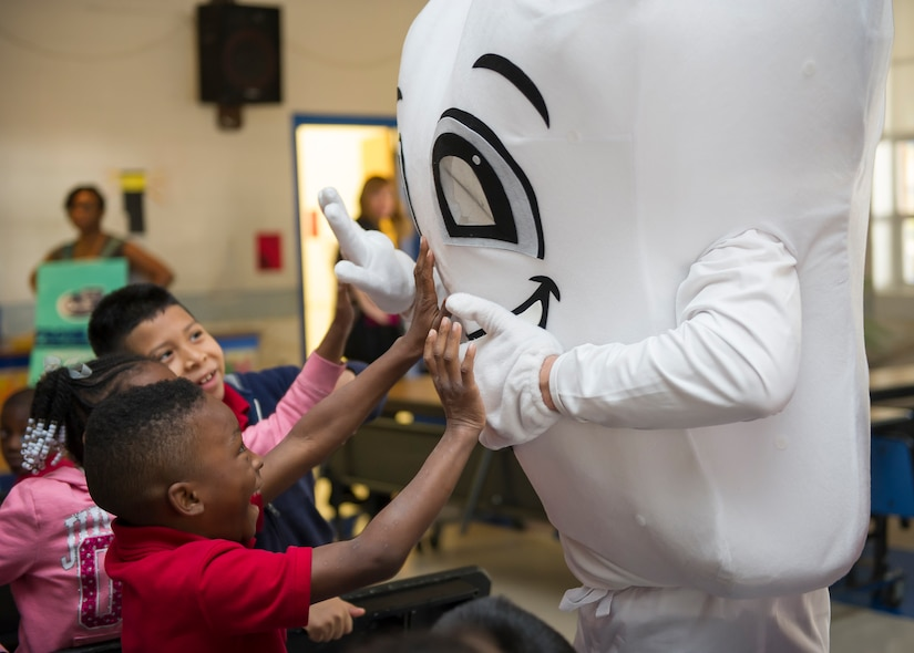 Patrick Miller, 628th Medical Group chief of preventative dentistry, interacts with children at Lambs Elementary School to promote good dental hygiene on Feb. 11, 2016. To ensure the presentation as child friendly, the dental clinic used a small cartoon instructional video, as well as a small skit where the dental clinic members dressed up as such things as a tooth, a toothbrush, dental floss, a tube of toothpaste and the tooth fairy. (U.S. Air Force photo/Airman 1st Class Thomas T. Charlton)
