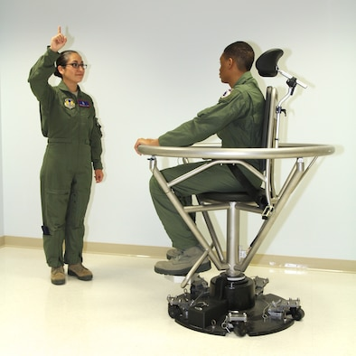 Tech. Sgt. Erica Luke uses her finger as a visual reference point for the student, Airman 1st Class James Jackson, an Aerospace and Operational Physiology technician, to focus on as he is spun in the Barany chair. This chair helps pilots with spatial disorientation that they could encounter when flying a plane. (U.S. Air Force photo/contributed)