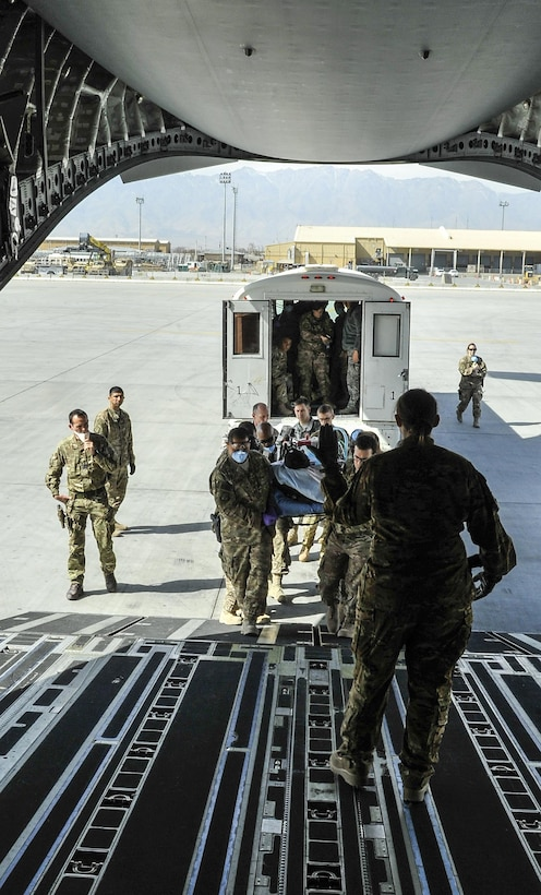 A 455th Expeditionary Medical Group team loads a NATO ally, who required Extracorporeal Membrane Oxygenation team support, onto an aeromedical evacuation transport at Bagram Air Field, Afghanistan, on Feb. 18, 2016. The ECMO team, dispatched from San Antonio Military Medical Center, uses technology that bypasses the lungs and infuses the blood directly with oxygen, while removing the harmful carbon dioxide from the blood stream. The patient was airlifted to Landstuhl Regional Medical Center, Germany, where he will receive 7 to 14 days of additional ECMO treatment. (U.S. Air Force photo by Tech. Sgt. Nicholas Rau)