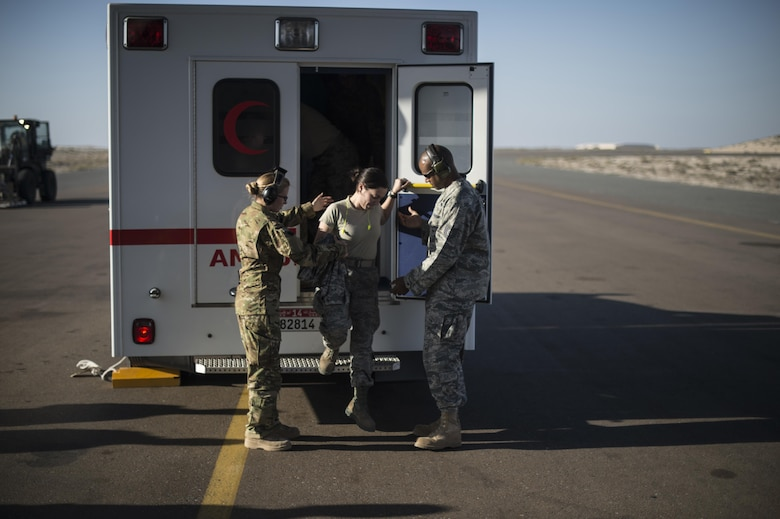 Members of the 379th Expeditionary Aeromedical Evacuation Squadron help a patient off an ambulance at an undisclosed location in Southwest Asia, Feb. 11, 2016. A typical 379th EAES mission includes transporting patients to locations with more definitive medical care or returning recovered personnel to duty at their deployed locations. (U.S. Air Force photo by Staff Sgt. Corey Hook/Released)