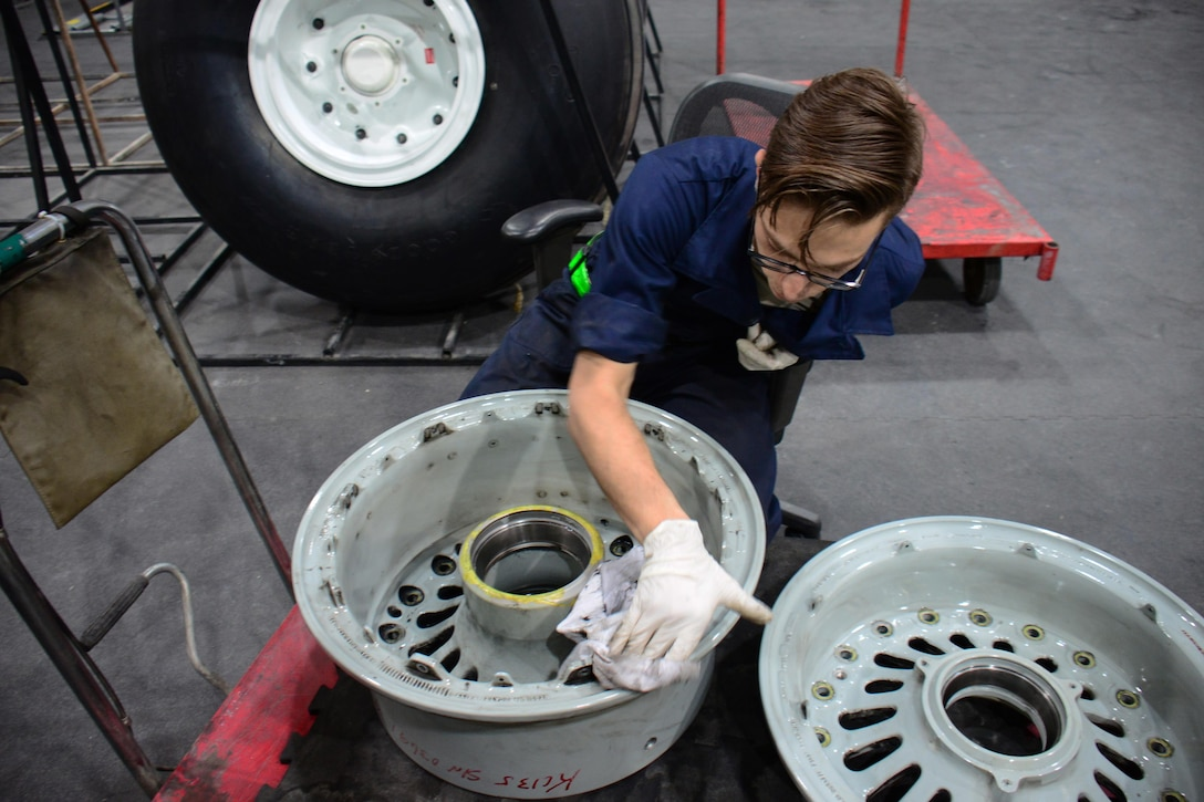 Senior Airman Michael Dalleo, 379th Expeditionary Maintenance Squadron aerospace maintenance apprentice, from Enfield, Connecticut, cleans a wheel at Al Udeid Air Base, Qatar Feb. 16. Cleaning every wheel by hand is part of the process of wheel and tire repair. During the cleaning process, Dalleo inspects the wheel for cracks and signs of corrosion. (U.S. Air Force photo by Tech. Sgt. James Hodgman/Released)