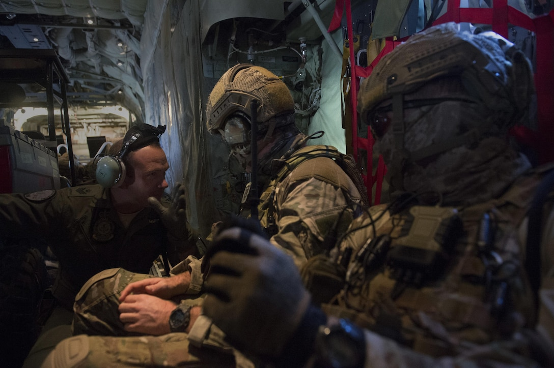 Royal Australian Air Force Sgt. Angus Shaw, a 37th Squadron loadmaster, left, talks with two 4th Squadron combat controllers aboard a C-130J Super Hercules during Exercise Cope North 2016 over Rota, Northern Mariana Islands, Feb. 12, 2016. Exercise The exercise includes 22 total flying units and nearly 3,000 personnel from six countries and continues the growth of strong, interoperable and beneficial relationships within the Asia-Pacific region through integration of airborne and land-based command and control assets. (U.S. Air Force photo/Staff Sgt. Matthew B. Fredericks)