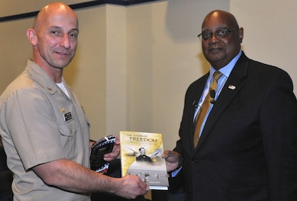 "DAHLGREN, Va. - Capt. Brian Durant, Naval Surface Warfare Center Dahlgren Division (NSWCDD) commander, presents the Dahlgren history book, ""The Sound of Freedom,"" to Dr. William Bundy, Gravely Naval Warfare Research Group director, at the 2016 Black History Month Observance, Feb. 11.  ""The research and development progress that was shared with me on the railgun and directed energy systems was very reassuring,"" said Bundy, a U.S. Naval War College professor who toured NSWCDD electromagnetic railgun and directed energy facilities after inspiring a military and civilian audience with his keynote speech at the observance. ""Those capabilities will certainly deliver advantages for our maritime forces.  It was absolutely encouraging to witness first-hand the remarkable effort and work that is continuing today at Dahlgren."""