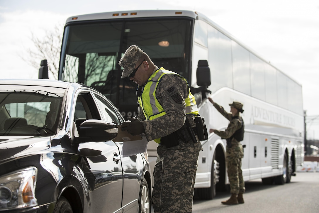 Sgt. Michael Villena (right), U.S. Army Reserve military police Soldier from Manassas Par, Va., with the 352nd MP Company, of the 200th MP Command, checks a driver's paperwork at one of the entry gates to Joint Base Myer-Henderson Hall, as part of a partnership training program with active duty Soldiers from the 289th MP Co., belonging to the 3rd U.S. Infantry Regiment (The Old Guard), to provide law and order, security and patrol support at various active duty installations in the Military District of Washington, D.C., Feb. 17. This partnership pilot program began in early February, placing Army Reserve Soldiers on active duty orders for three weeks while working at Joint Base Myer-Henderson Hall, Fort Lesley J. McNair and the Arlington National Cemetery. Soldiers will also support the Military District of Washington with additional duty days throughout the year. (U.S. Army photo by Master Sgt. Michel Sauret)